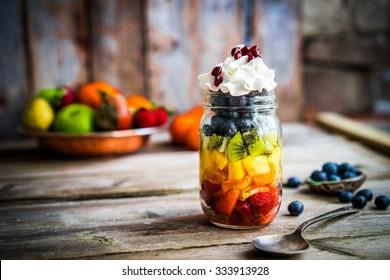 Farbiger Fruchtsalat in einem Glas auf rustikalem Holzhintergrund