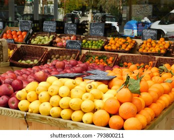 A colorful fruit shop in Greece, apples, lemons, oranges, kiwi fruit, lotuses, pears, pomegranates, limes, tangerines. The signs mean lotuses, pears, pomegranates, kiwi fruit, limes, Chios tangerines