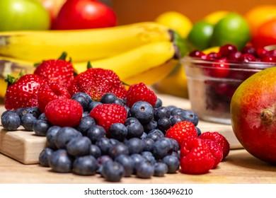 Colorful fruits including strawberries, blueberries, raspberries, mangoes, bananas, limes, lemons, apples, and cranberries