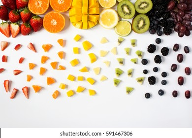 Colorful fruits in rainbow colors top view on the off white background: strawberries, blueberries, mango, orange, kiwis, blueberries