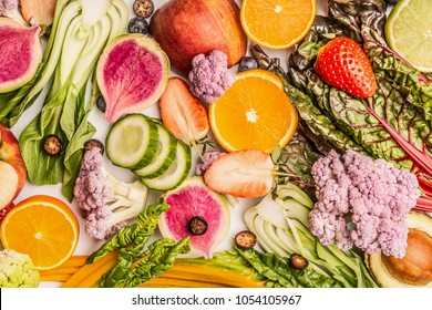 Colorful fruits and vegetables background with half of oranges, and berries , top view. Healthy food and clean eating ingredients concept