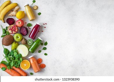 Colorful fruits and vegetables and bottles of smoothies or juices on white, copy space. Juice and smoothie ingredients. Healthy clean eating, detox, diet concept.
