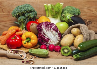 Colorful fruits, vegetables and legumes on wood background