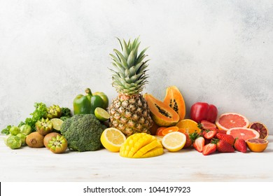Colorful fruits and vegetables rich in vitamin C in rainbow colors, oranges mango grapefruit kiwi kale pepper pineapple lemon papaya broccoli, on white table, copy space for text, selective focus