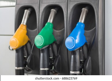 Colorful fuel pumps. Fuel nozzle at gas station. Concept of expensive gasoline. News about raising price of fuel