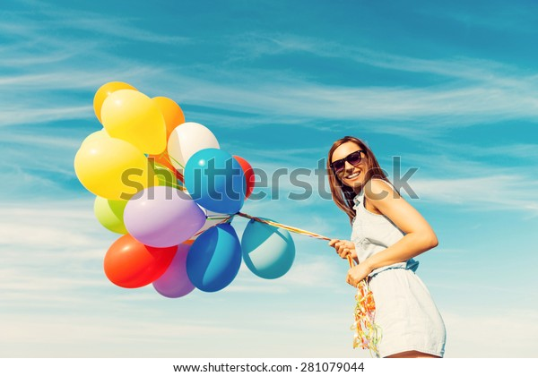 Colorful fun. Low angle view of happy young woman holding colorful balloons and smiling while standing against the blue sky