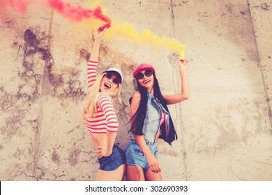Colorful fun. Two happy young women holding smoke bombs and smiling while posing against the concrete wall