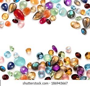 Colorful gems on white background. Many real polished stones: amethyst, sapphire, blue topaz, rainbow moonstone, labradorite, ruby, chalcedony, lapis lazuli, aventurine, peridot, rose quartz, citrine.