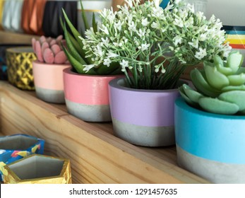 Colorful geometric planters on wooden shelf. modern beautiful painted concrete planters and succulent plants. Home and garden decoration concept.