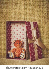Colorful gift box with the small soft toy lying on the couch