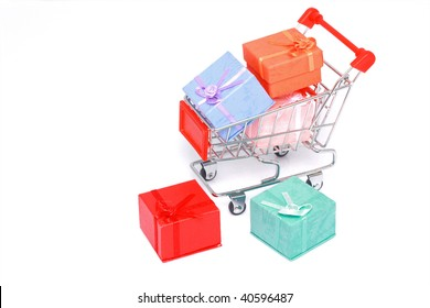Colorful gift boxes with miniature shopping cart isolated on white background.