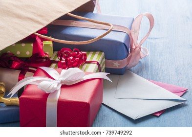 Colorful gifts and envelopes - Multitude of colorful gift boxes and  two envelopes coming out from a paper bag