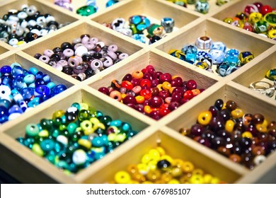 Colorful glass beads made in glassblowing workshop by masters. Variety of shapes and colors to make a bead necklace or a string of beads for women