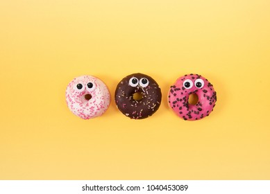 Colorful glazed donuts with funny eyes on yellow background. Creative minimal design.