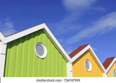 Colorful glowing houses front on the North Sea island Langeoog. Double pitch roof. Porthole, Bull's-eye. Blue shy with clouds.