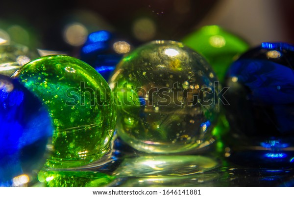 Colorful glowing orbs marbles on glass and water, closeup