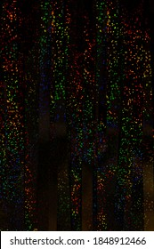 Colorful glowing rainbow drops and lights on black lined background. Abstract holographic backdrop. Black foil lines with multi-colored dotted shiny mini bokeh. Rainbow sparkle glitter.