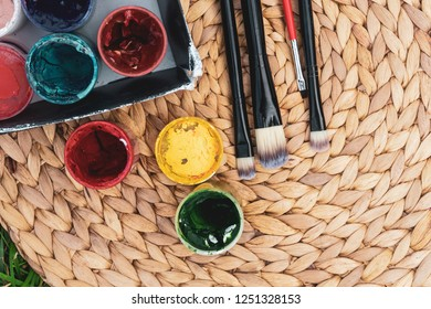 colorful gouache paint with tassels on a woven straw stand on the background of green glass