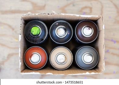 Colorful graffitty spray cans in a box