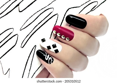 Colorful graphic manicure on an oval shaped nails are covered with black,white,red lacquer.