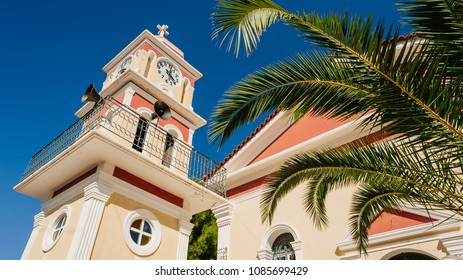 Colorful greek orthodox church bell tower with palm tree and deep blue sky, Cephalonia, Greece