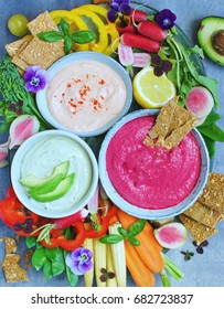 Colorful greek yoghurt dips with vegetables and crackers