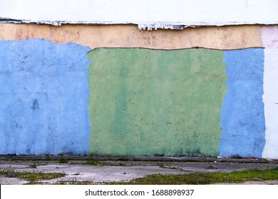 a colorful green and blue painted old factory warehouse wall in an alley