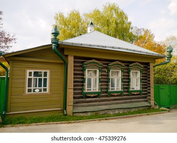Colorful green log house with metal roof in Russian village