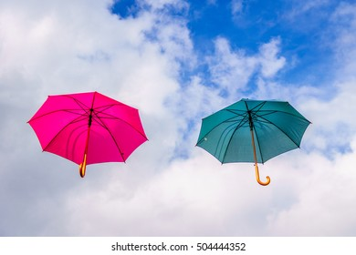 Colorful green and pink umbrella or parasol floating in the air under a partly cloudy sky