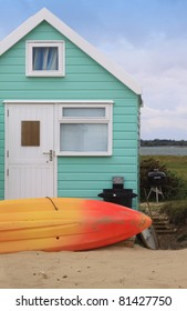 A colorful green wooden beech hut with an orange and yellow surf board resting in the sand to the front of the hut. Located in the South of England at Christchurch, Dorset, England.