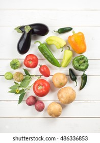 A Colorful Group of Nightshade Vegetables on rustic white vertical board background with room or space above and below for copy, text, your words.  Included are tomato, peppers, eggplant and potato