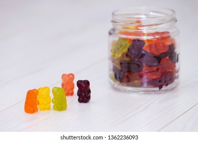 Colorful gummy bears on white wooden background. Collusion, friendship, treaty concept.