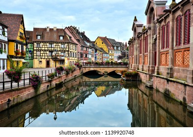 Colorful half timbered houses along a canal with reflections, Colmar, Alsace, France