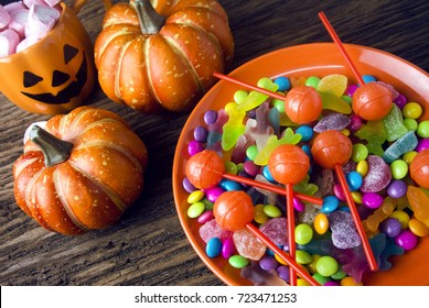 colorful of halloween candy with dessert on wood ground in party