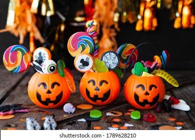 Bonbons d'Halloween colorés dans de petits paniers de citrouille souriants