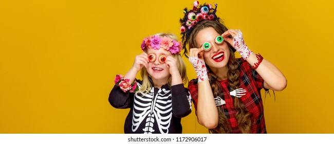 Colorful halloween. cheerful modern mother and daughter in Mexican style halloween costume on yellow background having fun time