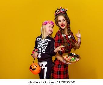 Colorful halloween. smiling modern mother and child in Mexican style halloween costume stealing candies isolated on yellow