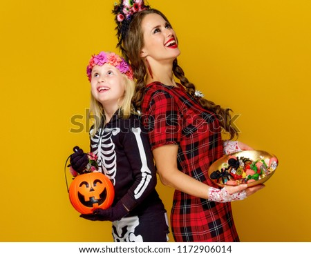 Colorful halloween. smiling modern mother and daughter in Mexican style halloween costume on yellow background with Halloween candies looking up at copy space