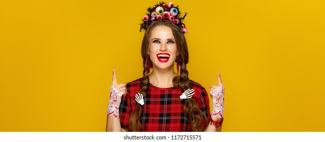 Colorful halloween. smiling young woman in Mexican style halloween costume on yellow background pointing up at something