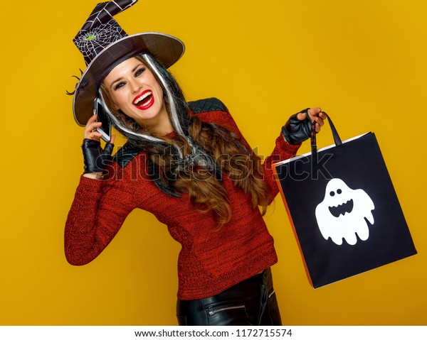 Colorful halloween. smiling young woman in halloween witch costume on yellow background with Halloween shopping bag speaking on a mobile phone