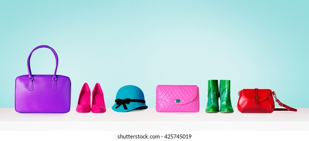 Colorful hand bags,shoes, and hat isolated on light blue background. Woman fashion accessories item. Shopping image.