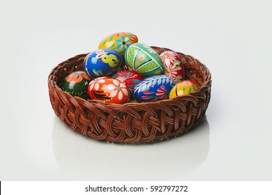 Colorful hand painted easter eggs in a wicker basket