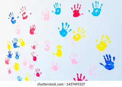 Colorful hand prints of hands isolated on white wall background. Children's handprints on school wall