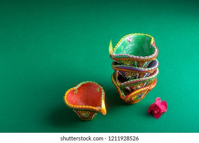 Colorful handcrafted traditional Diwali lamps stacked on eatch other. Beautiful Diwali festive background and objects.