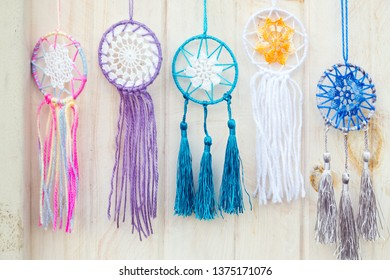 Colorful handmade dream catchers hanging on the white wooden wall