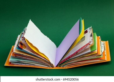 A colorful, handmade junk journal on green background. Made from a recycled box and  random paper such as book pages, envelopes and wall paper. Blank pages are shown.