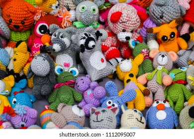 Colorful handmade knitted dolls. Hobby & small business of women. Closeup. Showcase at the fair