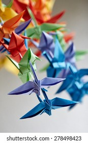 Colorful handmade origami cranes or fantasy birds, made of folded paper with complementary different colors, concept of joy, creativity and simplicity, close-up on gray