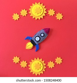 Colorful handmade rocket ship crafted with felt fabric. Yellow stars on red background with rocketship toy to DIY. Crafting supplies for hand made baby crib mobile for nursery. Happy colorful image.