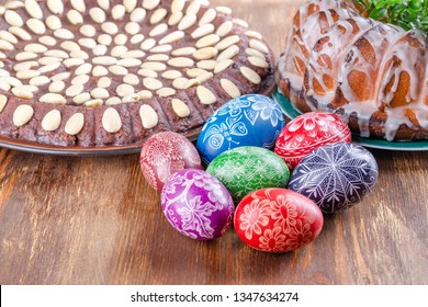 colorful handmade scratched easter eggs and easter cake on wooden table